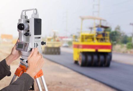 teodolito: trabajando con el equipo teodolito encuesta sobre un trípode mano. con carretera en fondo de la construcción