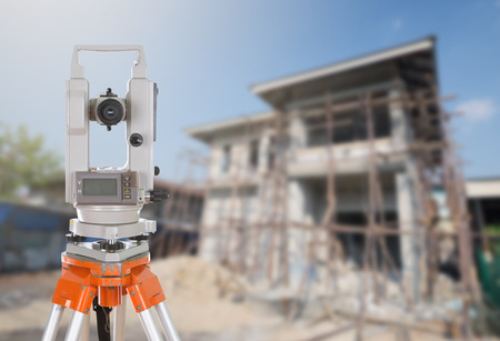 teodolito: Survey equipment theodolite on a tripod. with building construction site background