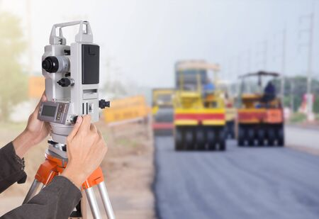 teodolito: hand working with survey equipment theodolite on a tripod. with road under construction background Foto de archivo