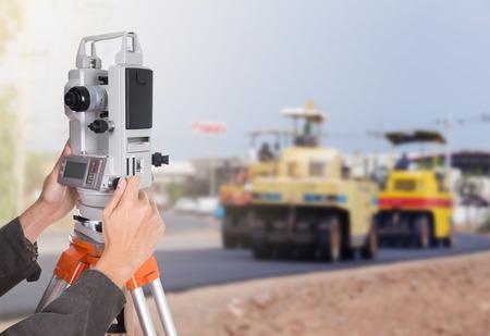 teodolito: trabajando con el equipo teodolito encuesta sobre un tr�pode mano. con carretera en fondo de la construcci�n