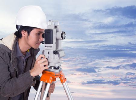 teodolito: ingeniero que trabaja con el equipo de encuesta teodolito con el cielo al atardecer Foto de archivo
