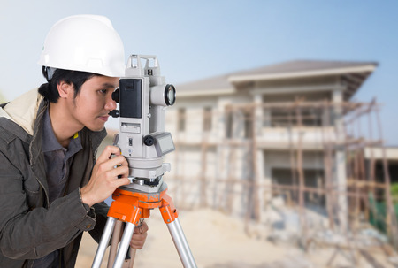 teodolito: Engineers use tacheometer or theodolite with building construction site background