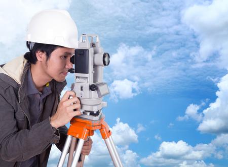 teodolito: ingeniero que trabaja con el equipo de encuesta teodolito con el fondo de cielo azul