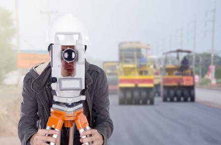teodolito: ingeniero que trabaja con el equipo de encuesta teodolito con carretera en fondo de la construcción