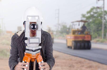 teodolito: ingeniero que trabaja con el equipo de encuesta teodolito con carretera en fondo de la construcci�n