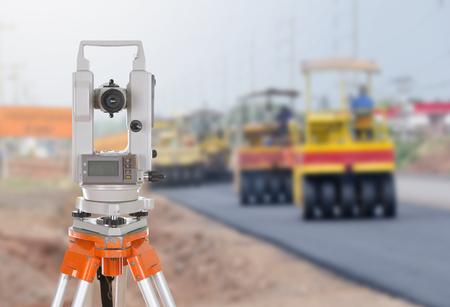 teodolito: Encuesta equipo teodolito en un trípode. con carretera en fondo de la construcción