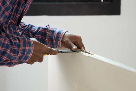 installer: carpenter installer works with hammer and chisel at wood door Stock Photo