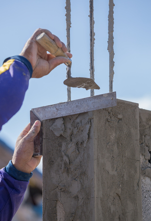 l hand: worker use iron ruler snd trowel plastering the poles at construction site