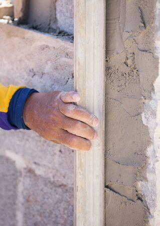 plasterwork: plasterer concrete worker at wall of house construction at construction site Stock Photo