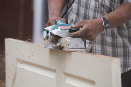 planing: worker planing a wood of door with an electric plane