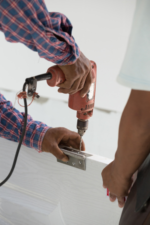 mounting holes: door installation. Worker drills a hole for the bolt of hinge