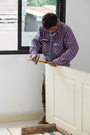 installer: NAKHON RATCHASIMA -JUNE 21 : carpenter installer works with hammer and chisel at wood door on June 21, 2016 in Nakhon Ratchasima, Thailand Editorial