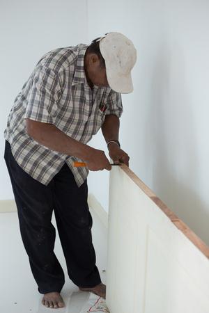 installer: NAKHON RATCHASIMA -JUNE 21 : carpenter installer works with hammer and chisel at wood door on June 21, 2016 in Nakhon Ratchasima, Thailand Stock Photo
