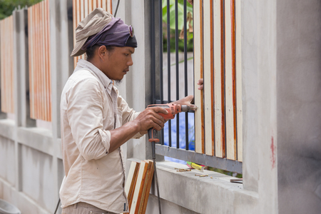 NAKHON RATCHASIMA -JUNE 21 : carpenter hands using electric drill on fence wood on June 21, 2016 in Nakhon Ratchasima, Thailand Stock Photo