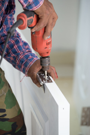 door installation. Worker drills a hole for the bolt of hinge