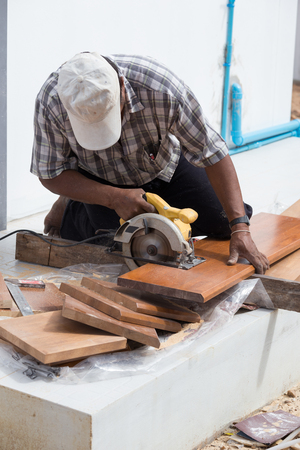 sawing: carpenter use electric saw to sawing wood board