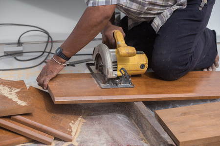 electric saw: carpenter use electric saw to sawing wood board