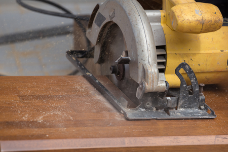 carpenter's sawdust: carpenter use electric saw to sawing wood board