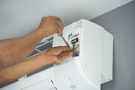 fixer: installation of the air conditioner, worker connects electric wires