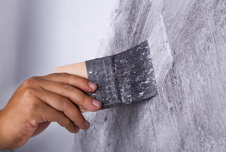 plasterwork: hand of worker use brush for color paint concrete Loft style on wall Stock Photo
