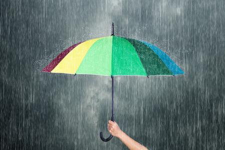 hand holding multicolored umbrella under dark sky with falling rain