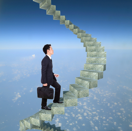 business man going upstairs in a curved staircase to success with blue sky background