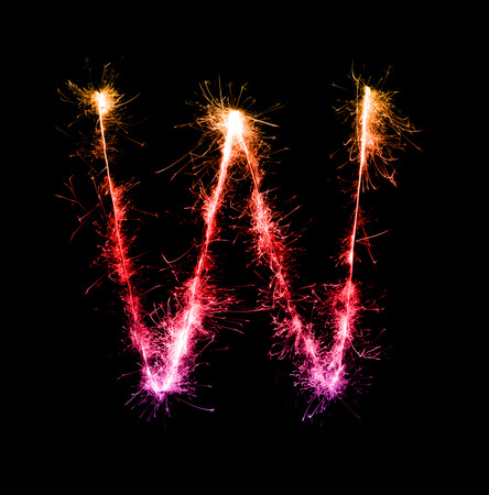 Sparkler firework light alphabet W at night background