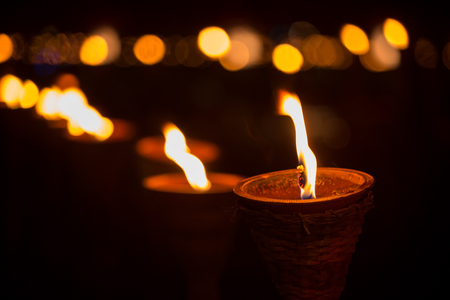 Traditional wooden torch flame with bokeh at night