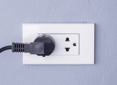 plugged in: black cable plugged in a white electric outlet mounted on gray wall background