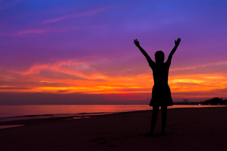 Silhouette of woman with hands up while standing on the sea beach at sunset Stock Photo