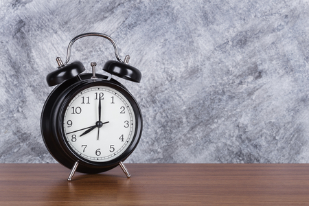 8 oclock vintage clock on wood table and concrete wall background Imagens