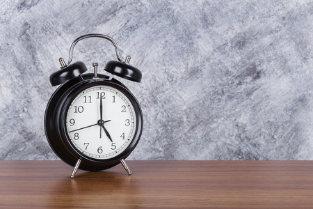 5 oclock vintage clock on wood table and concrete wall background