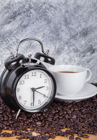 vintage clock and coffee in cup (Coffee time concept) with concrete wall background