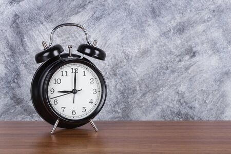 9 oclock vintage clock on wood table and concrete wall background