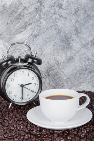 coffee in cup and vintage clock (Coffee time concept) with concrete wall background