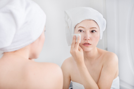 Beautiful woman looking mirror and cleaning her face with cotton