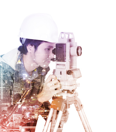 Double exposure of engineer working with survey equipment theodolite on a tripod against the city isolated on white background