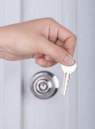 door knob: key in hand with door knob and white door