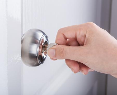Hand use the key for unlocking door knob on the white door Stock Photo