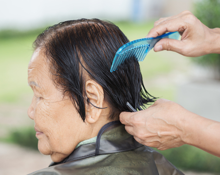 hand use comb to dressing the hair of a senior woman Banco de Imagens