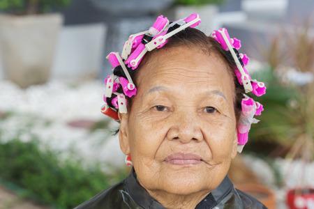 asian senior woman with hair roller