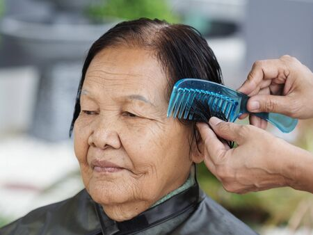 hand use comb to dressing the hair of a senior woman Stock Photo