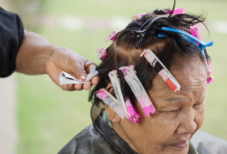 haircut: hand of a hairstylist doing a perm rolling the hair of senior woman Stock Photo