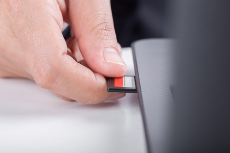 plugging:  hand inserting SD card into laptop slot