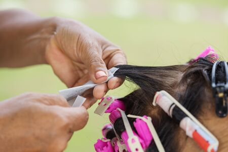 hand of a hairstylist doing a perm rolling the hair of senior woman Stock Photo