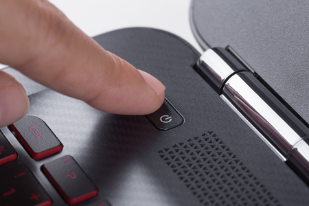 finger pushing power button on a laptop keyboard