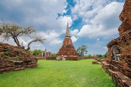 Ruins of buddha statues and pagoda of Wat Mahathat temple in Ayutthaya historical park, Thailand Stock Photo