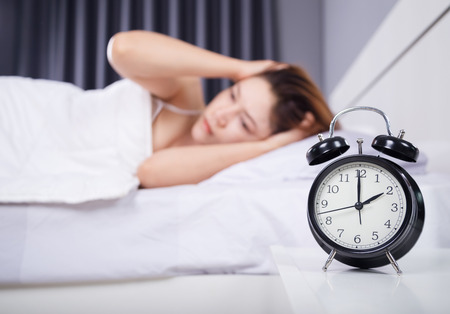 clock with woman sleepless on the bed