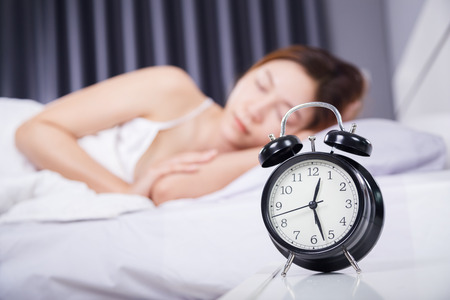 clock with woman sleeping on the bed Stock Photo