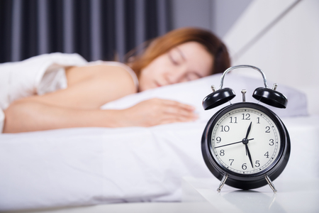 clock with woman sleeping on the bed Foto de archivo